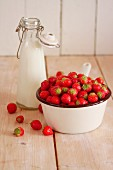 Strawberries in a saucepan next to a milk bottle