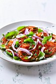 Tomatoes with capers, red onions and basil (close-up)