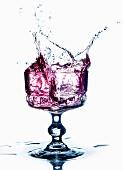 Violettes Getränk spritzt aus dem Glas