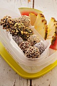 Fruit and nut balls, pineapple and watermelon in a Tupperware box