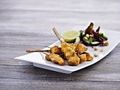Breaded chicken skewers with peanuts