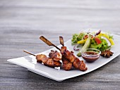 Chicken skewers with a spicy sauce and lettuce