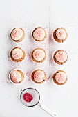 Raspberry and almond muffins decorated with buttercream and dried raspberry powder
