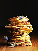 A stack of dried apple rings with borage flowers
