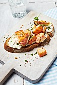 A slice of bread topped with salmon, cream cheese, figs and herbs on a chopping board