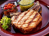 Grilled pork chop with tomato salsa and salsa verde