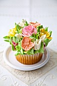 A cupcake decorated with romantic sugar flowers