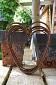 Rusty wire in the shape of a heart in front of vintage-style flower pots on a veranda
