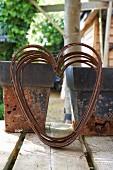 Herzform aus verrostetem Draht vor Blumentöpfen im Vintagestil auf Veranda