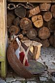 Kehrschaufel und Handbesen in rostiger Schale auf Pflasterboden vor Holzlager