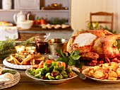 Traditional, country house-style Christmas dinner with a carved turkey and accompaniments