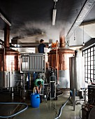 Two men working in a brewery with a large copper vat