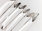 Cutlery wrapped in white napkins