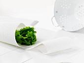 Grünes Salatblatt in Küchenpapier gerollt