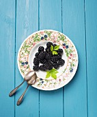 A plate of fresh blackberries with leaves