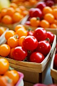 Red and yellow cherry tomatoes in wooden baskets