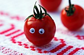 A tomato with eyes on a rustic tablecloth