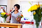 Young woman arranging flowers in kitchen