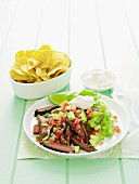 Tangy beef steak with avocado salsa and crisps