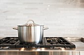 Saucepan on hob with splashback in kitchen