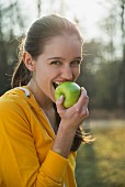 A young brunette woman biting into a green apple