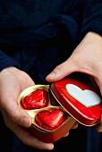 A hand opening a heart-shaped tin filled with red heart-shaped pralines