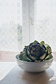 A bowl of artichokes on a sunny windowsill