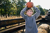 A little blond boy holding a pumpkin on his head