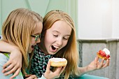A blonde girl trying to bite her friend's doughnut