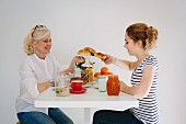 A mother and her teenage daughter having breakfast together
