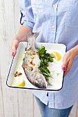 A woman holding fresh trout, herbs and lemons on a baking tray