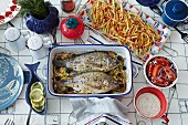 A view of a table with two roasted fish in a roasting tin, fries and salad