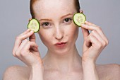 A portrait of a young woman with two slices of cucumber for an eye mask