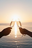 A couple toasting with champagne against sunset over the sea
