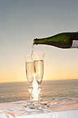 Champagne being poured into a flute against sunset over the sea