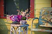 Rustikaler Metallstuhl & Blumenarrangement auf Beistelltischchen auf Veranda