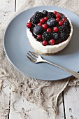 A mini cheesecake with blackberries, blueberries and redcurrants