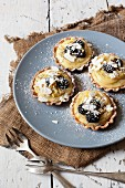 Blackberry tartlets with lemon cream, flaked almonds and icing sugar