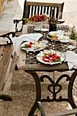 Gedeckter Terrassentisch mit Salattellern und Rotwein