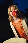 A little girl holding an apple between her teeth