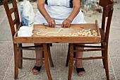 Apulische Frau bei der Herstellung von Orecchiette-Nudeln