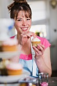 A young woman decorating a cupcake