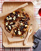 Caramelized onion pizza on a chopping board