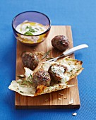 Lebanese meatballs on a chopping board with a dip