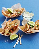 Seafood tempura with lime slices and a dipping sauce