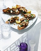 Bruschetta topped with mushrooms and spinach and served with lemon slices