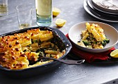 Pasticcio (Italian pasta bake) in a baking tin with one portion on a plate
