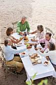 Blick auf drei Paare mittleren Alters im Freien bei Essen und Rotwein