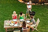 Junge Leute beim Grillen und Essen im Garten