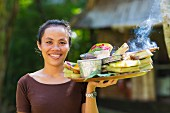 A Balinese woman carrying a tray of food